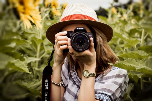 photography, woman holding camera in flower field