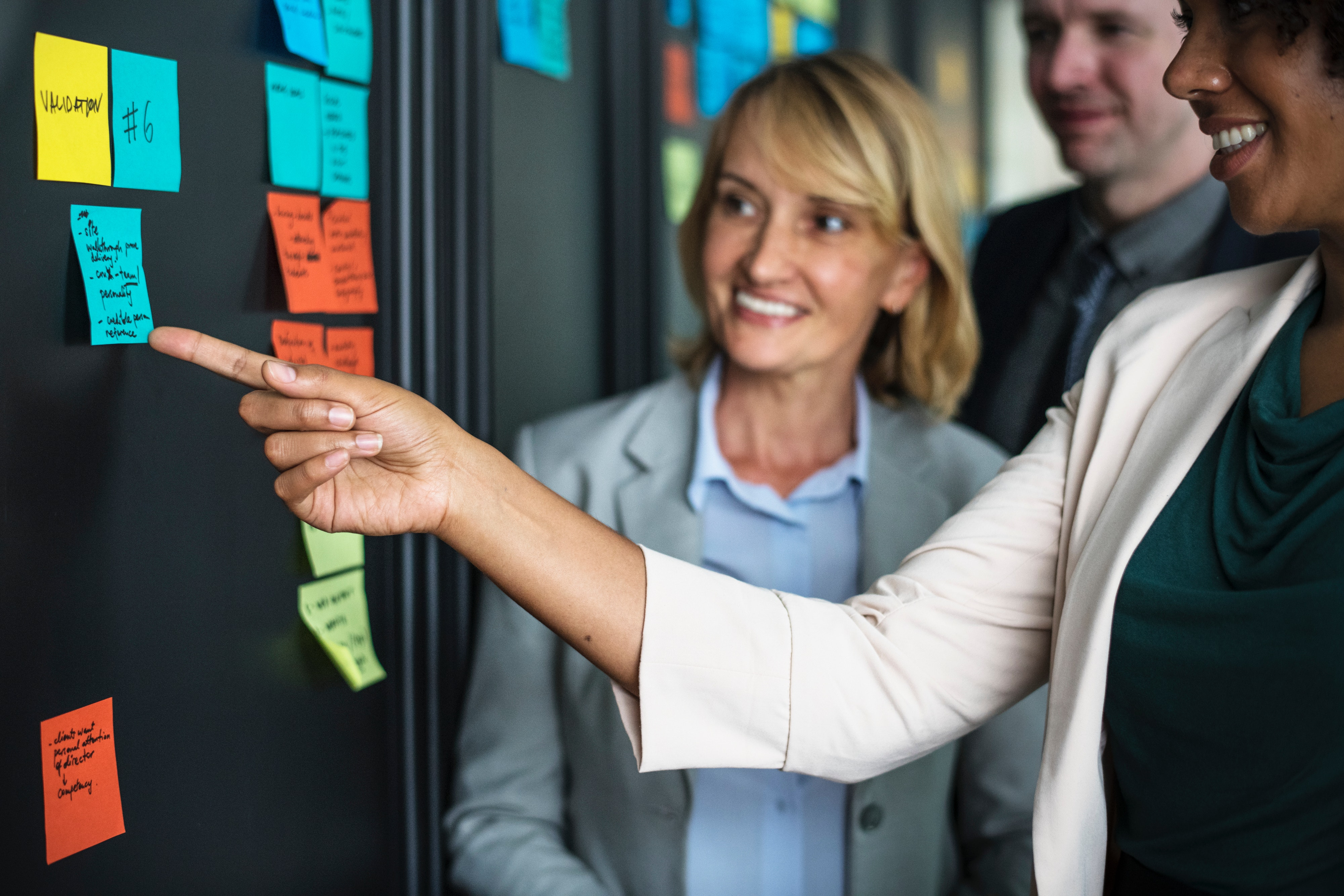 Employees, working, discussing topics on post-it notes