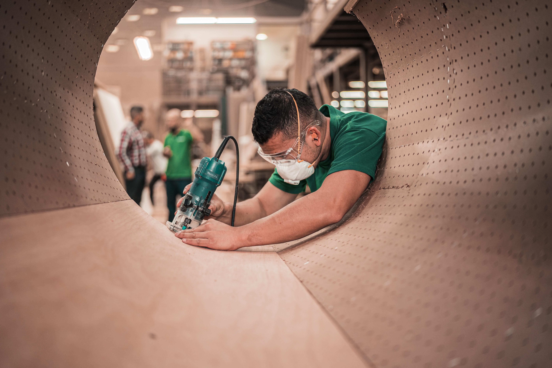 man in green shirt working